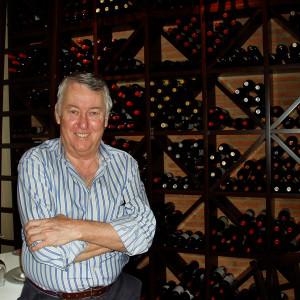 Manuel, el dueño de El Portichuelo, junto a la selección de vinos.
