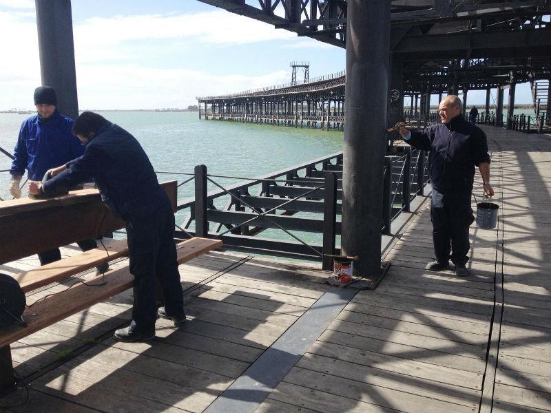 Los operarios realizan las labores de limpieza del Muelle.