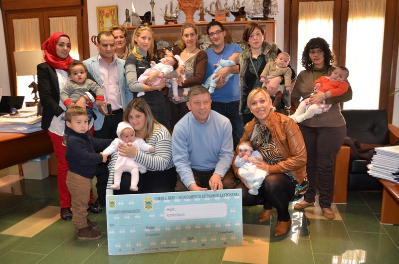 El alcalde de Palos rodeado de bebes beneficiarios del cheque.