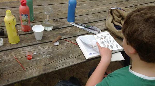 Un participante de la Escuela de Exploradores estudia las características del ave que está realizando en barro.