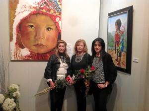 Las tres pintoras que exponen han creado conjuntamente el cuadro del fondo para ser rifado a beneficio de Madre Coraje.