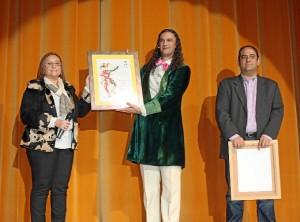 La alcaldesa entrega al pregonero un pergamino en presencia del presidente de 'Los Espaciales'.