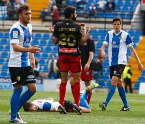 Un jugador del Hércules sobre el césped, mientras Menosse parece hablar con el árbitro. / Foto: José Navarro.