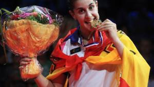 Carolina Marín muerde la medalla de oro conseguida. / Foto: www.badminton.es.