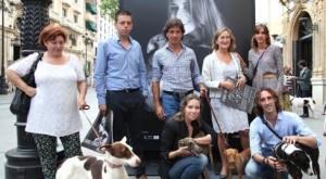 Rocío junto a algunos de los participantes y detrás el mupi de su foto con Benji, uno de los galgos que ya ha sido adoptado.