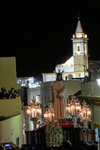 La imagen del Jesus Cautivo, en su retorno al templo, con torre de la Parroquia en un segundo plano
