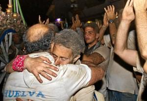 Dos romeros se abrazan a su llegada a la aldea. / Foto: Julián Pérez.