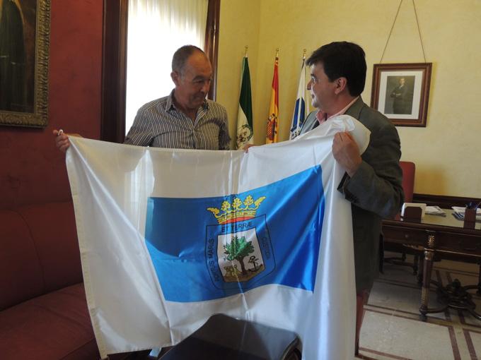 Cruz entrega a Ruiz una bandera de Huelva.
