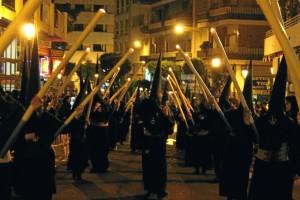 El silencio marca el caminar de la cofradía por el centro de Huelva.