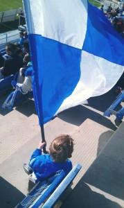 Roque, con una bandera blanquiazul, animando al Recreativo.