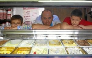 Javier Moya, en su heladería de Moguer con niños de la Asociación Abriendo Puertas.