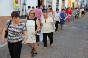 Mujeres con velas de promesas delante del paso.