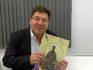 El alcalde de Trigueros, Cristóbal Romero, con la revista editada con motivo de las Fiestas de San Antonio Abad, donde se puede ver el cartel anunciador de estos días festivos.