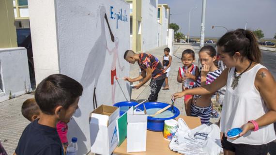 Un total de 18 niños de la Escuela Municipal de Verano de Marismas del Odiel decoran los muretes del barrio