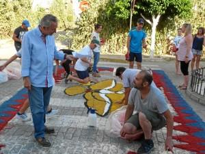Trabajando en la realización de alfombras de serrín teñido con motivo de la celebración del Corpus en Hinojos.