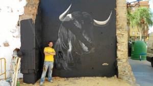 El artista urbano, Víctor Romero 'Konestilo', junto a uno de sus trabajos junto a la Plaza de Toros de la Merced.