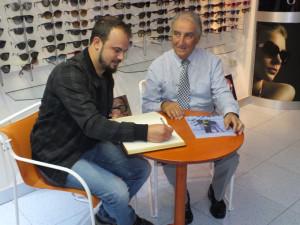 Firmando en el libro de visitas de la Óptica.