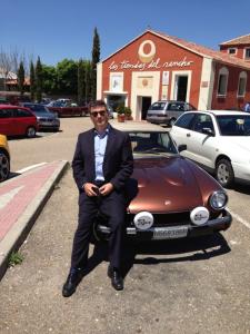 Con un Fiat 124 spider, que pone de manifiesto su afición a los coches y motos antiguas.