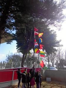 Izada de banderas durante el acto de inauguración.