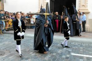 Los nazarenos visten túnica, capa, morrión y escapulario azul marino.