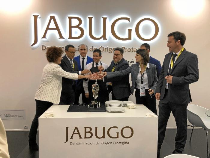 Expositor en la Feria Alimentaria ofreciendo uno de los productos típicos de Huelva, el jamón de Jabugo.