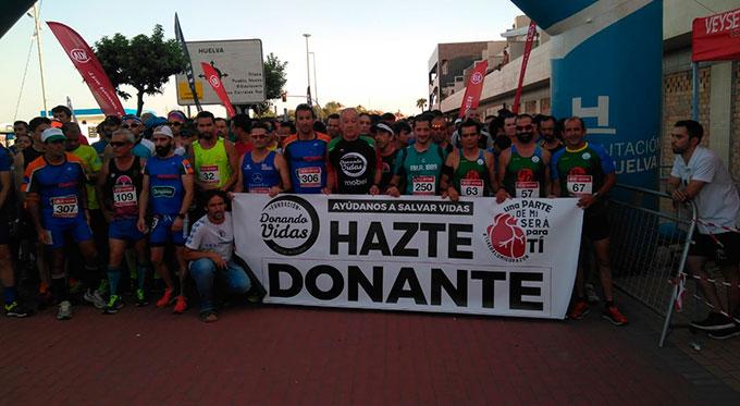 Los participantes de la prueba en Corrales, en los momentos previos a la salida, con una pancarta alusiva al fin solidario.