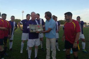 El concejal de Deportes de Punta Umbría, Juan José Iglesias, entrega un obsequio al equipo inglés de veteranos.