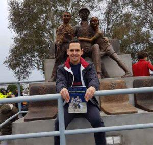 Juan Manuel Garrido Anes, con el libro 'No quiero verte llorar. Cuando Huelva resucitó al Decano' del que es autor, delante del monumento.