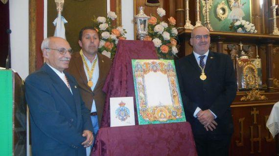 La Hermandad de Emigrantes presenta su nueva orla de cultos y el escudo del cincuentenario