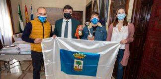El alcalde Gabriel Cruz entregó a Daniel Marín la bandera de Huelva y le felicitó por el triple oro conseguido.