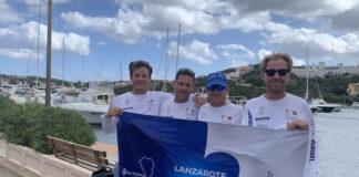 De izquierda a derecha, Rafa Lasso, Nete Armas, Ricardo Terrades y Tomás Fuentes del 'Lanzarote-Wacaf Air' sosteniendo una bandera con mensaje de apoyo a la isla de La Palma.